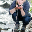 A hiking young blond woman refreshes itself in to a brook — Stock fotografie