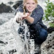 A hiking young blond woman refreshes itself in to a brook — Stock Photo