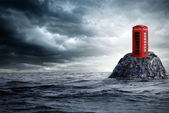 Red telephone box lonely in the ocean — Stockfoto