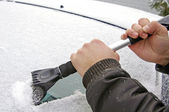 Scraping snow and ice from the car windscreen — Stock Photo
