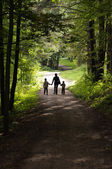 Women and two childrens walking on a forest path — Stock Photo