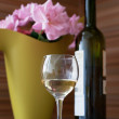 Flowers, a bottle and a glass of wine — Stock Photo
