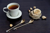Cup of tea and two stylish teaspoons — Stock Photo