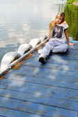 Young beautiful woman sitting on a pier — Stock Photo