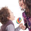 Kids licking a lollipop — Stock Photo #23965041