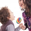 Kids licking a lollipop — Stock Photo