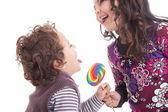 Kids licking a lollipop — Stock Photo