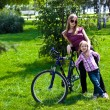 Happy young mother with her daughter riding bicyc — Stock Photo