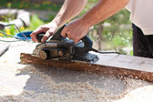 Carpenter with electric planes — Stock Photo