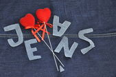Hearts on the background of blue jeans. — Stock Photo