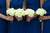 Four bridesmaids holding white rose wedding bouquets — 图库照片