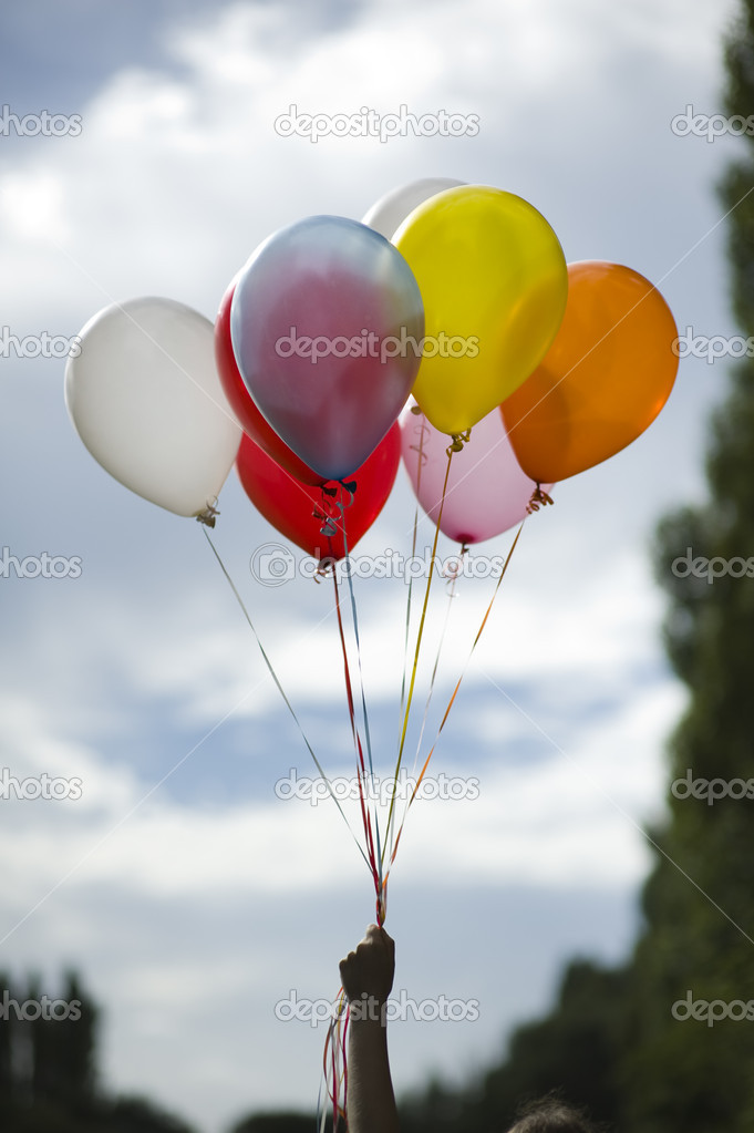 Person holding colored helium balloons — Stock Image © eelnosiva #