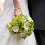 Bride holding wedding flowers — Stock Photo #13615001