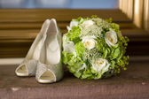 Wedding shoes and flowers bouquet — Stock Photo