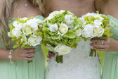Bridesmaids in green with wedding bouquet — Stock Photo