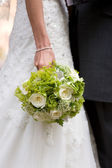 Bride holding wedding flowers — Stock Photo