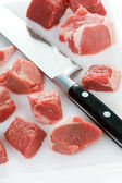Dicing raw lamb with a kitchen knife — Stock Photo