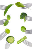 Border of fresh green vegetables isolated on forks — Stock Photo