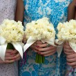 Stock Photo: Three daffodil wedding bouquets held by bridesmaids