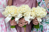 Three daffodil wedding bouquets held by bridesmaids — Stock Photo