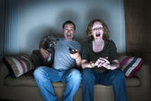 Middle aged couple and dog laughing at the television — Stock Photo