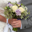 Bride and groom holding a wedding bouquet — Stock Photo