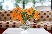 Orange lilies in a vase — Stock Photo