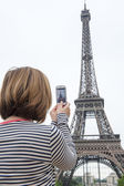 Woman taking photographs of eiffel tower paris using a cellphone — Stock Photo