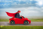 Senior superhero driving a toy sports car — Stock Photo