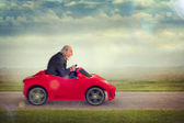Senior man driving a toy racing car — Stock Photo