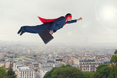Superhero businessman flying above a city  — Stock Photo