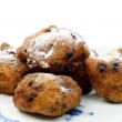 Powdered Dutch oliebollen baked with currents on a blue and white plate — Stock Photo #11841273