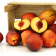 Fresh nectarines and a cut one in a wooden crate — Stock Photo