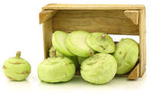 Freshly harvested kohlrabi and a cut one in a wooden crate — Stock Photo