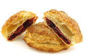 Delicious puff pastry cherry turnovers and a cut one — Stock Photo