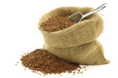 Flax seed (linseed) in a burlap bag with an aluminum scoop — Stock Photo