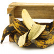 Sweet ripe baking bananas (plantain bananas) and a peeled one in a wooden crate — Stock Photo