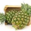 Fresh pineapple fruits in a wooden crate — Stock Photo