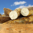 Cassava root and some pieces in a wooden crate — Stock Photo #27525479