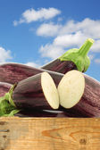 Mixed aubergines and a cut one in a wooden crate — Stock Photo