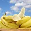 Fresh bananas and a peeled one in a wooden crate — Stock Photo