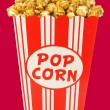 Caramel popcorn in a decorative paper popcorn cup — Stock Photo