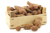 Bunch of topinambur roots (helianthus tuberosus) in a wooden crate — Stock Photo