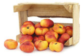 Flat nectarines in a wooden crate — Stock Photo