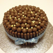 Постер, плакат: Chocolate birthday cake with maltesers chocolate fingers and white chocolate balls on a silver cake base for a birthday party the cake will be cut into slices and shared with family and friends