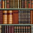 Old library of vintage hard cover books on shelves — Stock Photo #41609181