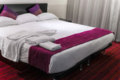 Contemporary hotel room suite queen size bed — Stock Photo