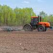 Stock Photo: Tractor cultivating the field