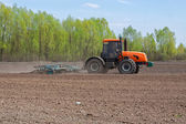 Tractor cultivating the field — Stock Photo