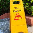 Sign with caution wet floor near the swimming pool - Stock Photo